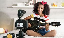 Girl recording herself singing and playing guitar